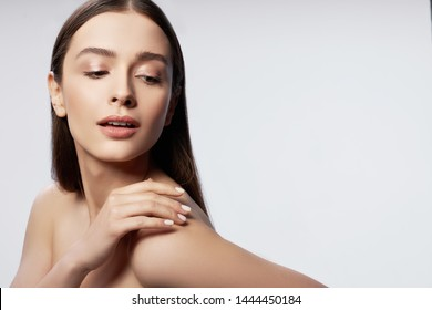 Waist up portrait of attractive woman touching her skin and keeping lips slightly parted. Copy space in right side