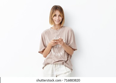 Waist up portrait of attractive young female adult wears oversized t-shirt, looks with delightful expression, going to run, listens music in earphones, isolated on white. People, lifestyle concept