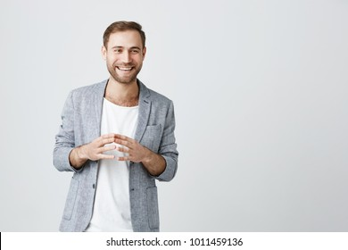 Waist up portrait of bearded male in gray jacket over white t-shirt keeping his fingers together looking with smile at camera during conversation. Man in trendy clothes having pleased look
