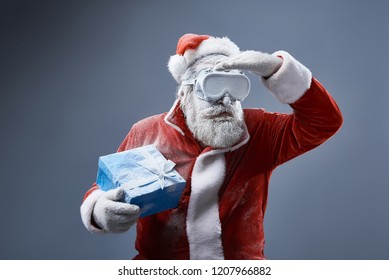 Waist up portrait of bearded old man in Santa costume covered with snow holding blue gift box. He is trying to find the right path