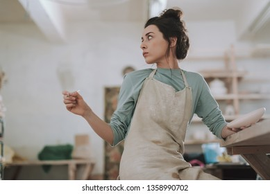 Waist up portrait of beautiful brunette lady in apron holding paint brush and ceramic plate while sitting at the table. She turning back and looking away with serious expression