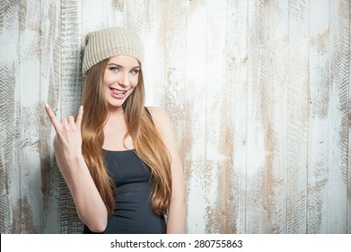 Waist up portrait of beautiful hipster girl with nice hat, who is showing a gesture that symbolizes adoring rock and metal, impertinently smiling and grimacing showing her tongue expressing all her