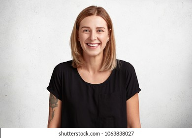 Waist up portrait of beautiful smiling young woman with positive expression, wears casual black t shirt, has tattooed arm, models against concrete wall, happy to recieve present from best friend