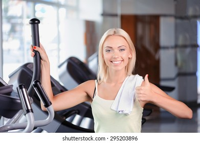 Waist up portrait of a beautiful young blond girl wearing a white top with a towel on her shoulder looking at the camera and showing thumb up, standing on a treadmill smiling in a fitness club