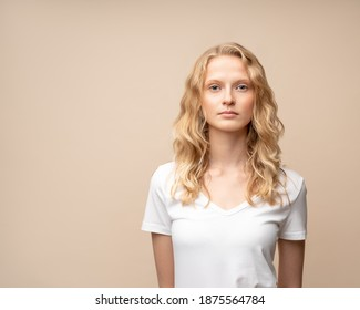 Waist up portrait of beautiful young serious clever blonde woman without makeup on beige wall. Pretty female with curly hair in white t shirt