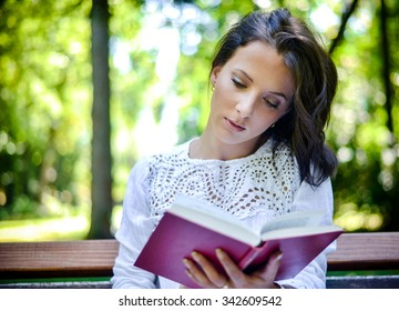 Waist Up Portrait of Brunette Woman Wearing Lace Top Engrossed in Novel Outdoors in Idyllic Tranquil Forest Setting