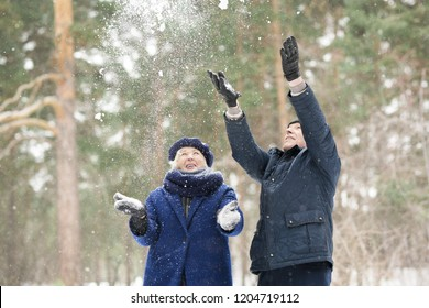 Waist up portrait  of carefree senior couple playing with snow in winter forest, copy space