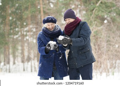 Waist up portrait  of carefree senior couple holding handfuls of snow in winter forest and laughing happily, copy space