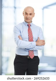 Waist up portrait of casual businessman with arms crossed standing at office while looking at camera.