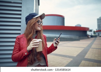 Waist up portrait of charming red-haired girl in glasses holding cup of coffee while reading messages on smartphone and smiling