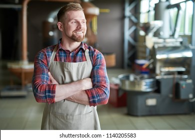 Waist up portrait of cheerful bearded man wearing apron posing standing confidently with arms crossed against roasting machines in artisan coffee roastery, copy space