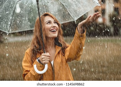 Waist up portrait of cheerful girl holding umbrella and catching rain drops with smile. She is stretching hand and looking upwards with sincere delight