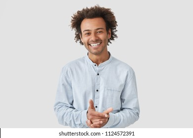 Waist up portrait of cheerful handsome African American male keeps hands together, smiles broadly, dressed in elegant shirt, being in high spirit after date with girlfriend, shares impressions