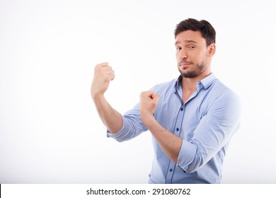 Waist up portrait of cheerful man making his hands in fists and stretching it aside. He is confident and boastful.  Isolated on a white background and there is copy space in the left side