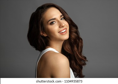 Waist up portrait of cheerful pretty young woman with alluring appearance posing at studio. Sensual female in white shirt with delicate make-up looking at camera with happiness and calmness