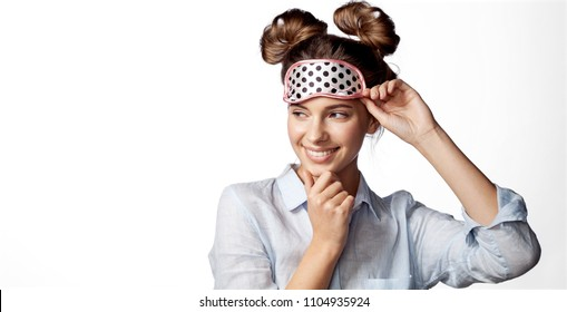 Waist up portrait of cheerful smiling girl in sleeping mask. Attractive funny female in stylish pajama standing and looking away. Isolated on white background