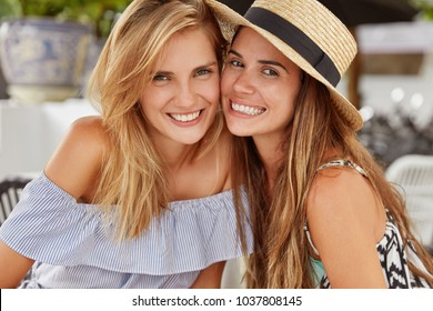 Waist up portrait of cheerful young women have pleasant satisfied expressions, pose at camera, enjoy togetherness and good rest. Gay couple relaxes at terrace cafeteria. Friendship, relations concept