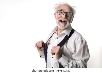Waist up portrait of comical tousled pensioner standing in suspenders looking at camera and laughing. Copy space in left side. Isolated on background