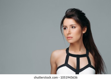 Waist up portrait of confident stylish lady in fashion blouse. Pretty brunette with amazing brown eyes and delicate makeup. She is looking in camera with seduction. Isolated on gray background
