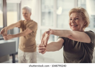Waist up portrait of content mature female doing hand stretching exercise. Elderly man standing beside her in same posture. Focus on lady