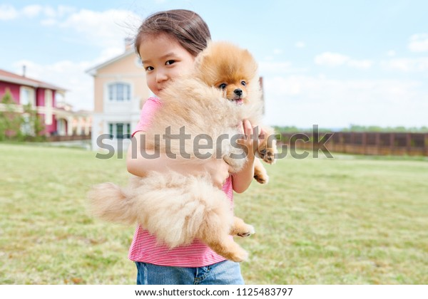 Waist up portrait of cute Asian girl posing with Pomeranian puppy standing in front yard of two storey house, copy space