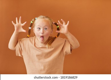 Waist up portrait of cute girl with down syndrome making faces at camera while standing against plain brown background in studio, copy space