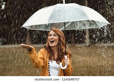 Waist up portrait of delighted girl standing outside and hiding under umbrella. She is stretching hand catching water drops with joy