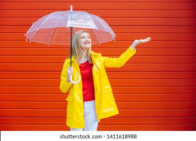 Waist up portrait of delighted girl in yellow raincoat, red t-shirt standing outside and hiding under umbrella over red garage background. Cute expression on face. Weather forecast concept