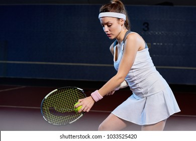 Waist up portrait of determined young woman serving ball while playing tennis in indoor court, copy space