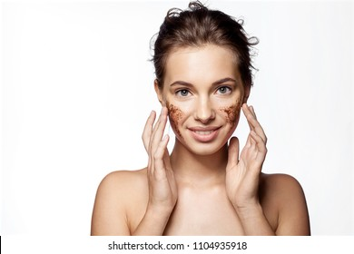 Waist up portrait of engaging girl with peeling cosmetic product on beauty face. Smiling female doing spa procedure. Skincare concept. Isolated on white background