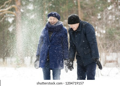 Waist up portrait  of excited senior couple playing with snow in winter forest and laughing happily, copy space