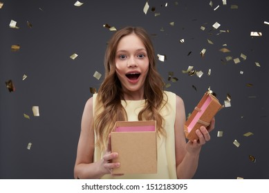 Waist up portrait of excited young lady with present looking at camera with wide open mouth. Isolated on blue-gray background with foil confetti