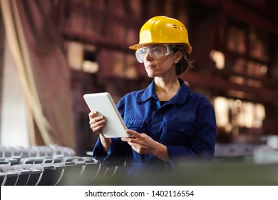 Waist up portrait of female worker using digital tablet while supervising production at plant, copy space