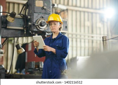 Waist up portrait of female worker wearing hardhat looking at camera while standing by machines in workshop, copy space