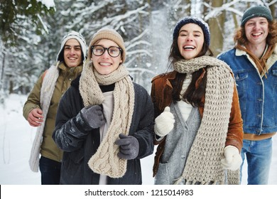 Waist up portrait of four carefree young people running towards camera while having fun in winter forest during vacation