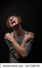 Waist up portrait of frustrated junkie sitting with arms crossed on chest, he is looking up and crying. Isolated on background
