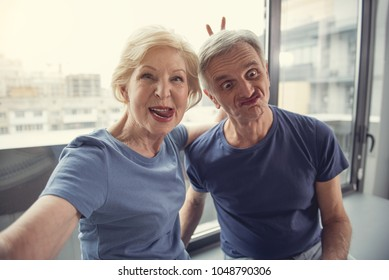 Waist up portrait of funny old man and woman photographing themselves and making faces