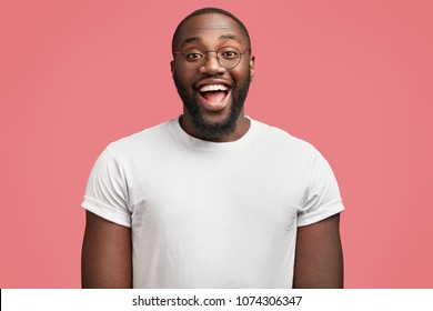Waist up portrait of glad dark skinned handsome male model with happy expression, wears round spectacles, being in good mood as recieve bonus for diligent work, isolated over pink background