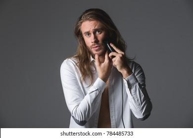 Waist up portrait of good looking man running razor along cheek. Isolated on grey background