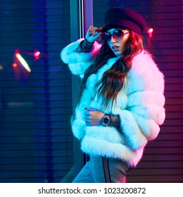 Waist up portrait of gorgeous female model wearing large round sunglasses, cap and stylish white half-length fur coat posing on street. Lovely smiling long haired woman in fashionable outfit.