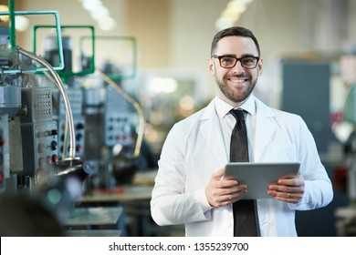 Waist up portrait of handsome factory worker holding digital tablet posing  in workshop and smiling happily at camera, copy space