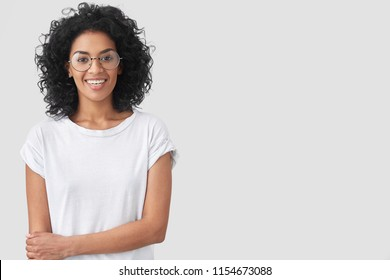 Waist up portrait of happy dark skinned female with Afro hairstyle, smiles gently, being glad to recieve good news, wears casaul white t shirt, stands against studio wall, copy space for advertisement