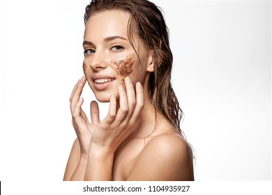 Waist up portrait of happy girl with beauty scrub on face. Sensual female applying natural coffee mask for exfoliating and moistening. Perfect fresh clean skin concept. Isolated on white background