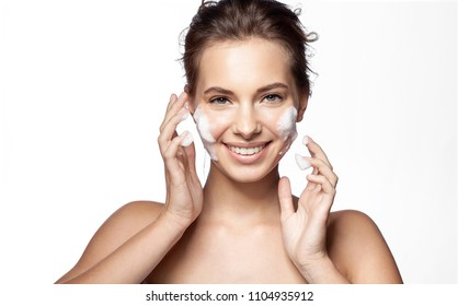 Waist up portrait of happy laughing girl with foam for washing on her face. Cheerful female looking at camera with gladness. Perfect fresh clean skin concept. Isolated on white background