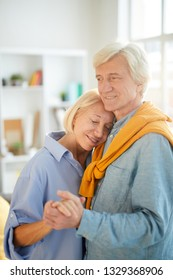 Waist up portrait of happy senior couple dancing at home lit by sunlight