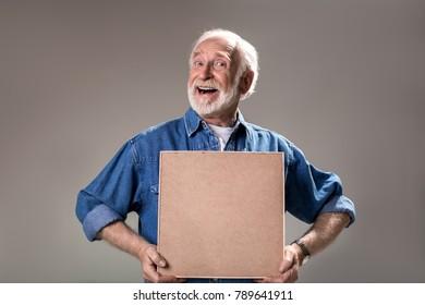 Waist up portrait of humorous elderly man holding wooden frame. Isolated on grey background