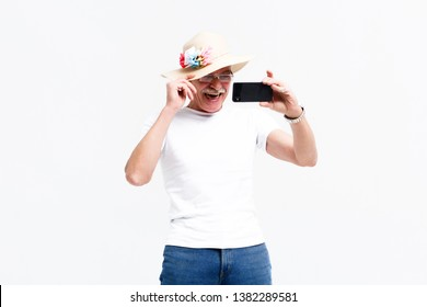 Waist up portrait of jolly oldster making selfie and holding up bonnet Isolated on background.