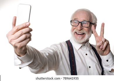 Waist up portrait of jolly oldster making selfie and holding up two fingers. Isolated on background