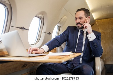 Waist up portrait of joyful businessman in airliner working on his computer while talking by cellphone