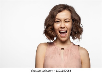 Waist up portrait of joyful girl with nice hairdo and perfect make-up. Joyous cute female with amazing smile looking at camera with happiness. Copy space in left side. Isolated on white background